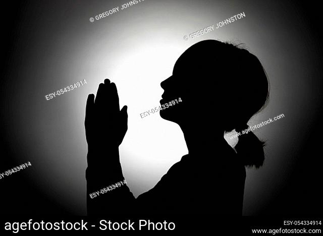 The silhouette of a girl bowed in prayer