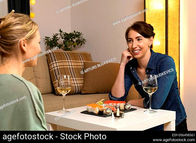 Two women friends sitting by table and eating sushi. Family, friendship and communication concept