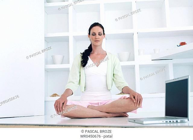 Mid adult woman meditating on the floor