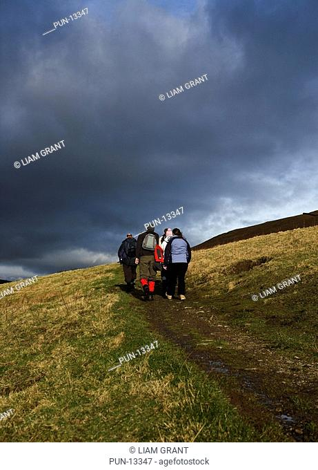 Group of walkers on route to Gowbarrow Fell and Dockray from Aira Force in winter Gowbarrow Park, Dockray, Lake District, Cumbria, UK