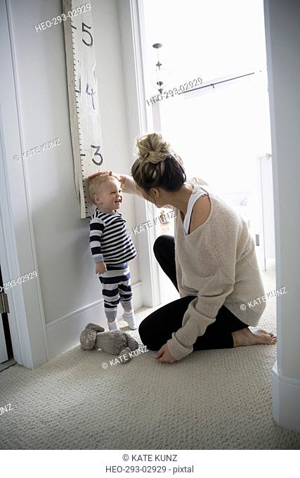 Mother measuring baby son height
