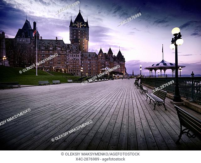 Boardwalk of Dufferin terrace and the Fairmont Le Château Frontenac castle at dusk with dramatic night sky and street lights