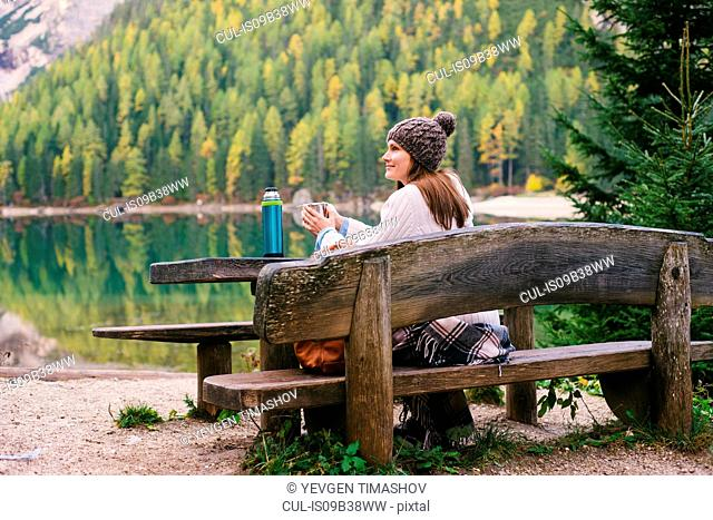 Woman relaxing on park bench, Lago di Braies, Dolomite Alps, Val di Braies, South Tyrol, Italy