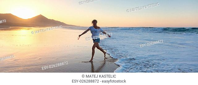 Woman having fun runing from waves on solitary sandy beach in sunset. Waves sweeping away her traces in sand. Beach, travel, concept