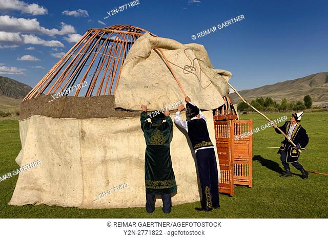 Men in traditional dress assembling wool felt covers over Yurt frame in Saty Kazakhstan