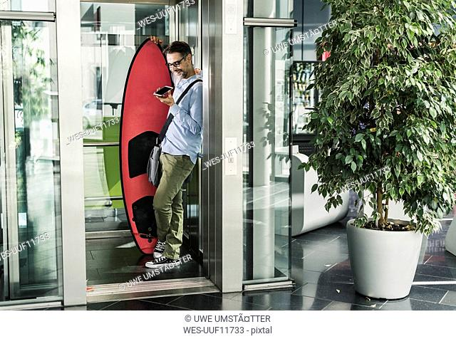 Smiling businessman with surfboard and cell phone in elevator