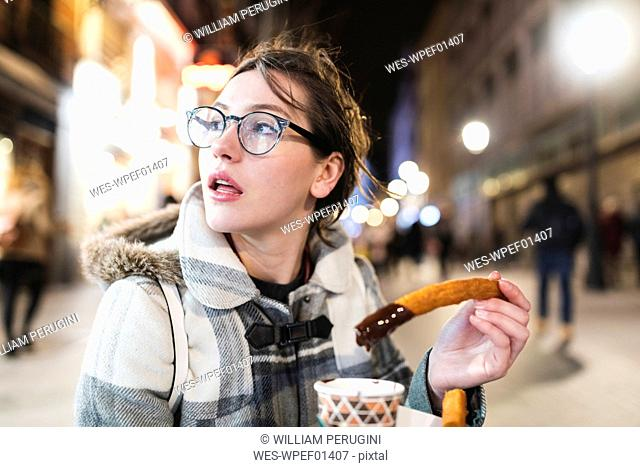 Spain, Madrid, young woman in the city at night eating typical churros with chocolate