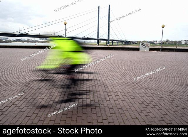 03 April 2020, North Rhine-Westphalia, Duesseldorf: A single cyclist is on his way along the banks of the Rhine. Public life is currently suffering from the...