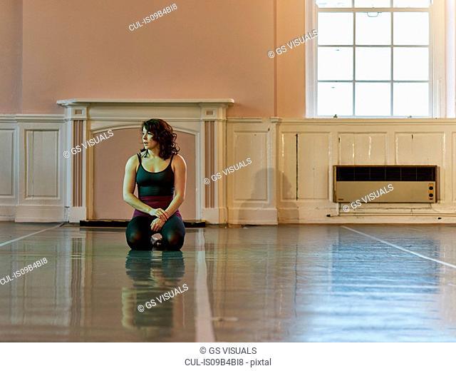 Young female acrobat kneeling on practice floor