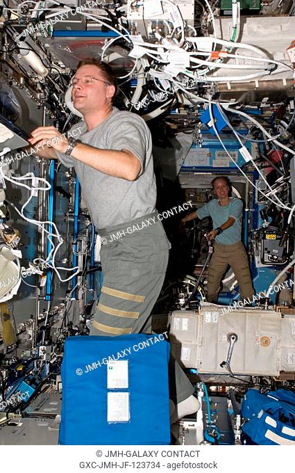 NASA astronauts Doug Wheelock and Shannon Walker, both Expedition 24 flight engineers, work in the Destiny laboratory of the International Space Station