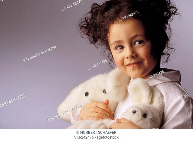 portrait, indoor, 8-year-old girl with brown curly hair and brown eyes wearing a white dress holding her 2 white plushy toys in her hand  - GERMANY, 26/02/2005