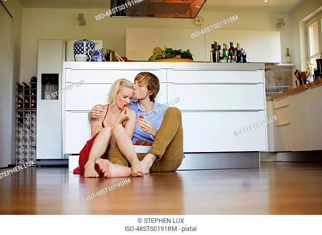 Couple eating strawberries on floor