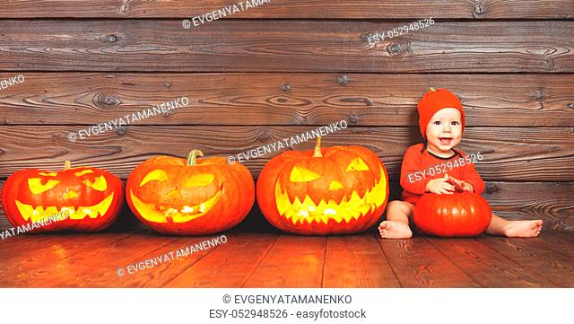 happy baby in costume for Halloween with pumpkins with burning eyes on wooden background