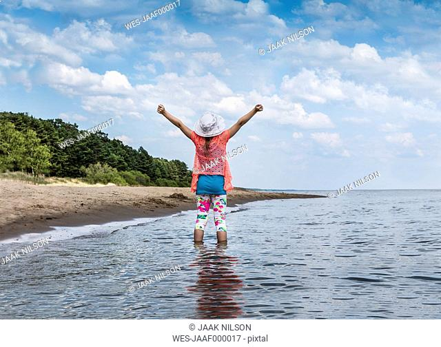Estonia, Lake Peipus, girl in water with raised arms