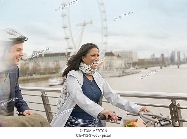 Smiling, carefree couple bike riding on bridge near Millennium Wheel, London, UK