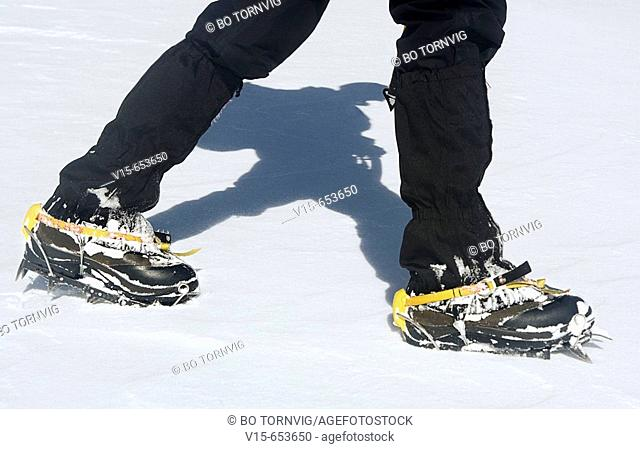 Mountaineer in snow covered mountain with crampons