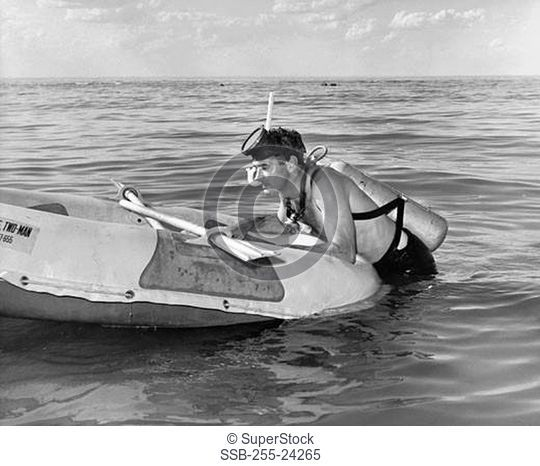 Young man leaning on inflatable raft
