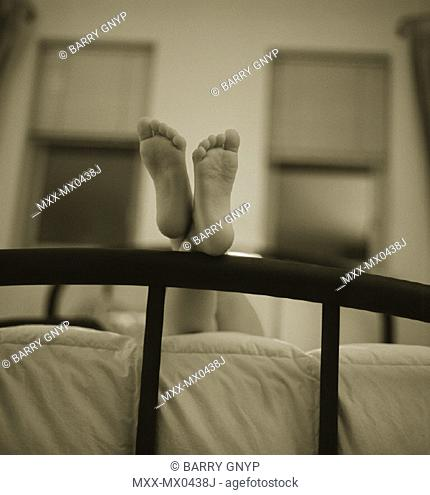 Feet resting on bed frame