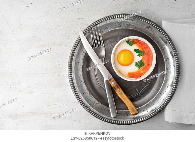 Eggs baked with tomatoes and parsley in the ramekins with cutlery top view