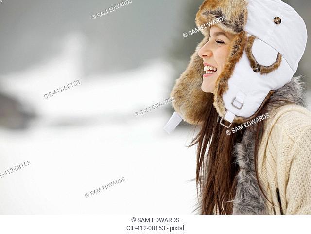 Happy woman wearing fur hat in snow