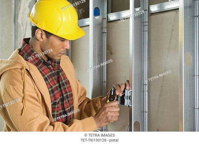 African male electrician installing wires