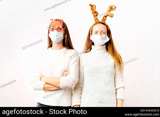 Caucasiam young women on white background with santa hat and reindeer. Christmas quarantine. High quality photo
