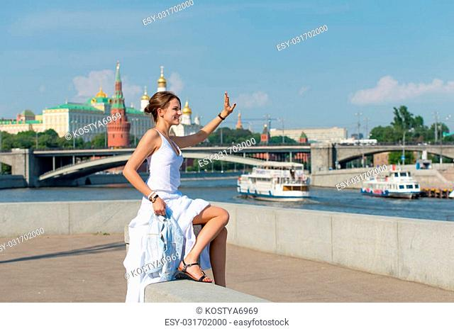 Beautiful girl in white dress strolls along the river on the background of the Moscow Kremlin