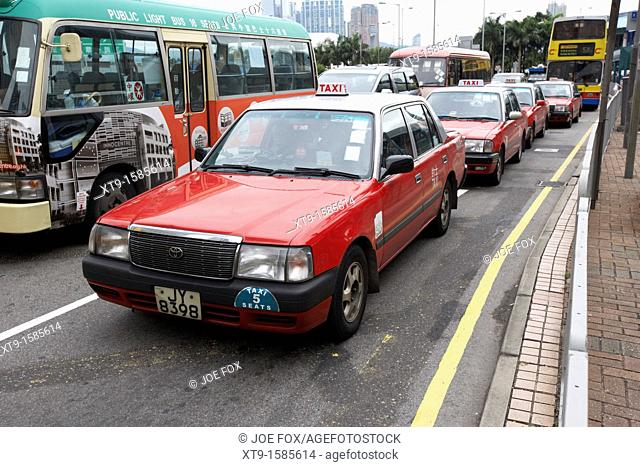 row of hong kong red taxis and public transport busses central district hong kong island hksar china