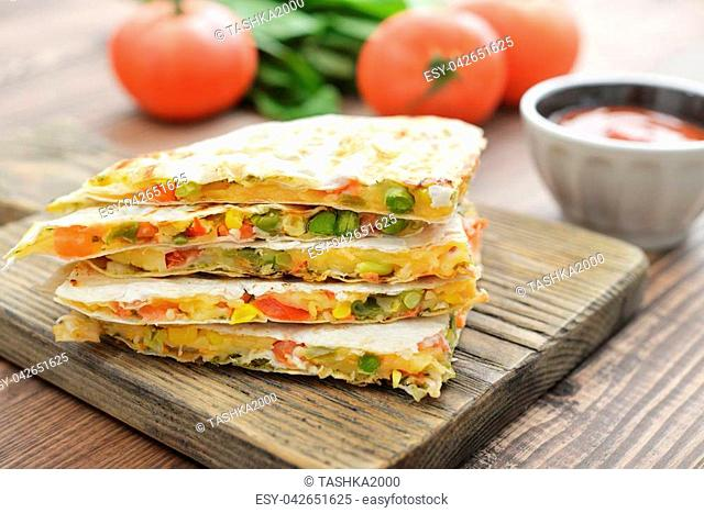 Stack of mexican Quesadilla with chicken, corn, sweet pepper and tomato closeup
