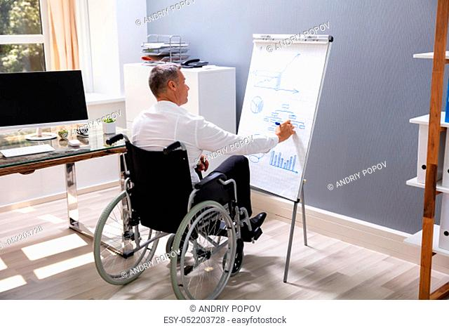 Handicapped Businessman Sitting On Wheelchair In Office Drawing Diagram On Flipchart