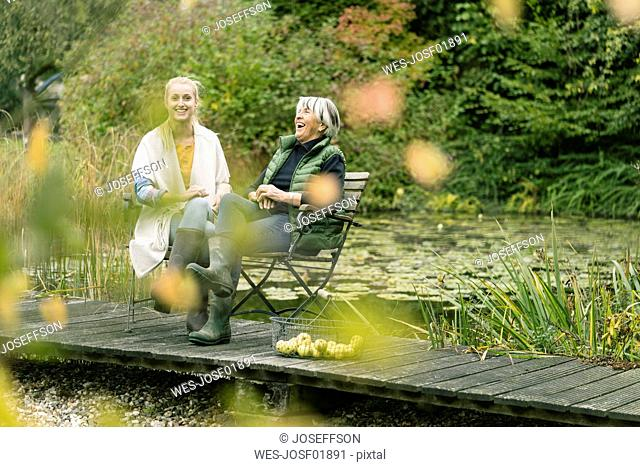Happy young woman with her grandmother sitting on jetty at garden pond