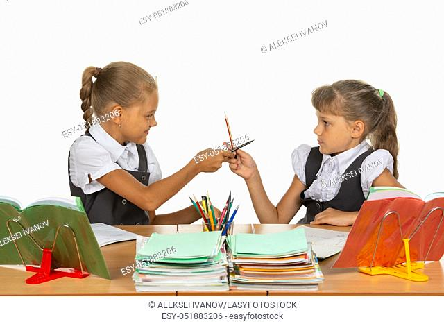 Two girls fight with pencils at a school desk