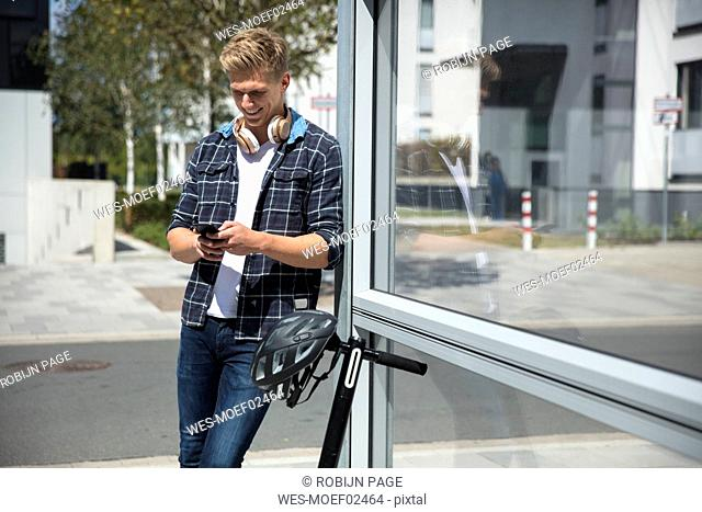 Young man with e-scooter using cell phone in the city