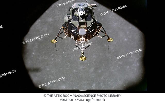 The LEM flies away from the Command Module window revealing the full extent of it's insect-like appearance, it's gold Mylar foil glistening in the Sunlight