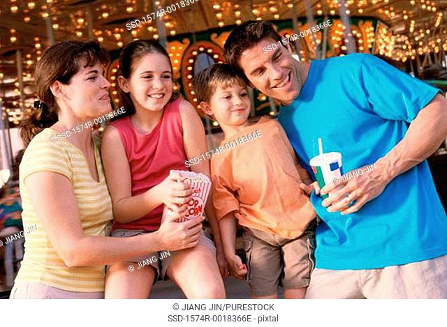 Close-up of parents with their son and daughter in an amusement park
