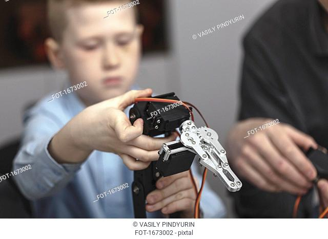 Boy operating machinery while sitting by teacher at table in classroom