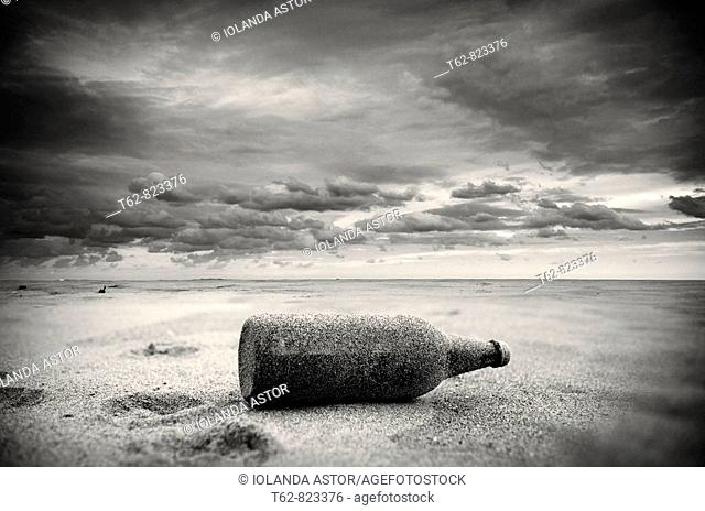 Bottle left in the sand of the beach after the storm