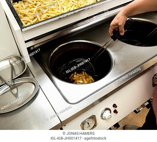 A man preparing french fries in a Belgian traditional fritkot
