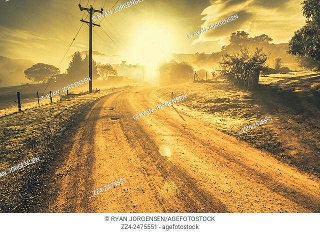 Dusty small town road leading into the haze of a mist covered dawn. Judbury, Tasmania, Australia