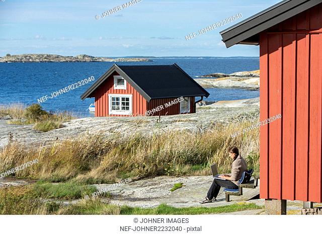 Woman using laptop at coast