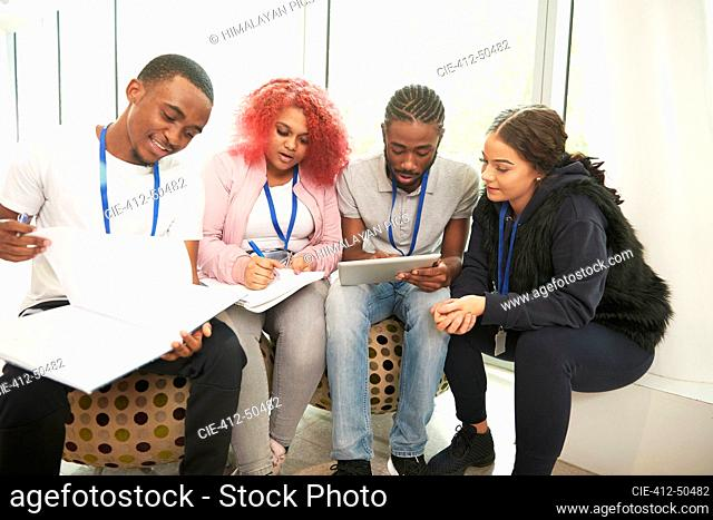 College students with notebooks and digital tablet studying