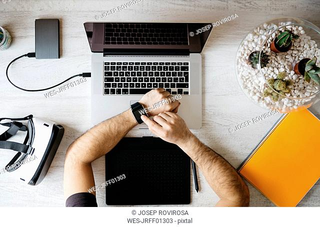 Man using smartwatch at desk, top view