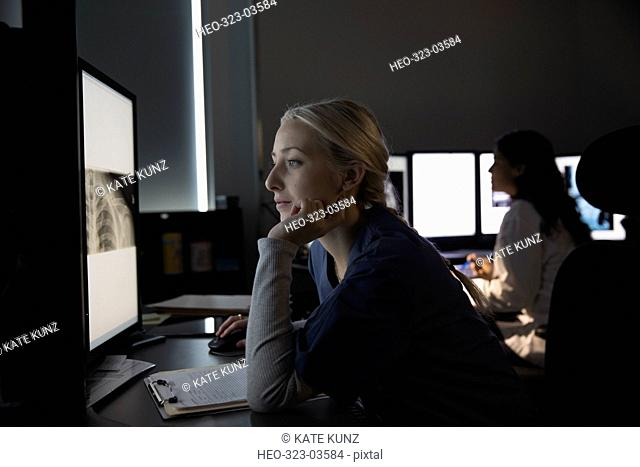 Focused female nurse reviewing digital x-ray on computer in dark clinic doctor