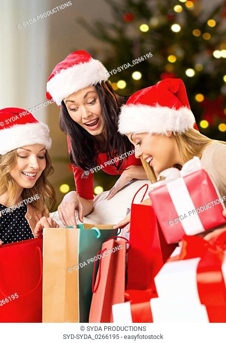 women in santa hats with gifts on christmas