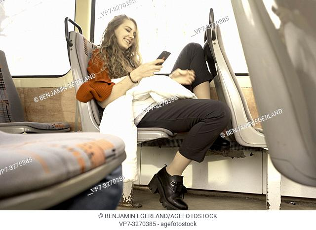 young woman sitting in public transport, using phone, in city Cottbus, Brandenburg, Germany