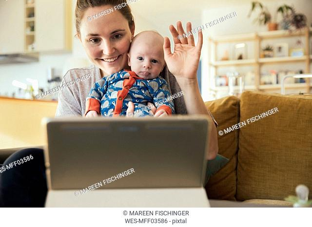 Mother and newborn baby taking a video call at home