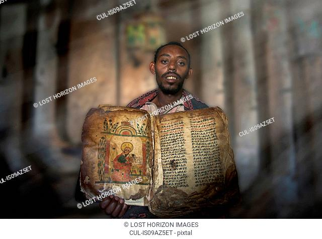 Priest showing an ancient religious book in an orthodox monastery, Tigray, Ethiopia