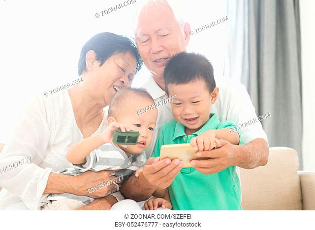 Portrait of happy Asian grandparents and grandchildren taking self photo using smart phone at home, family indoor lifestyle