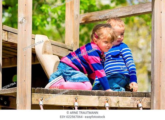 Mädchen und Junge auf einem Klettergerüst