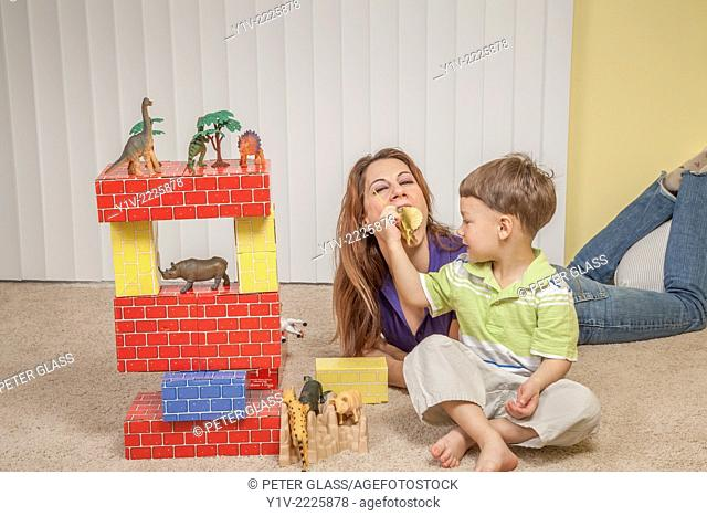 Mother and young son playing with his toys